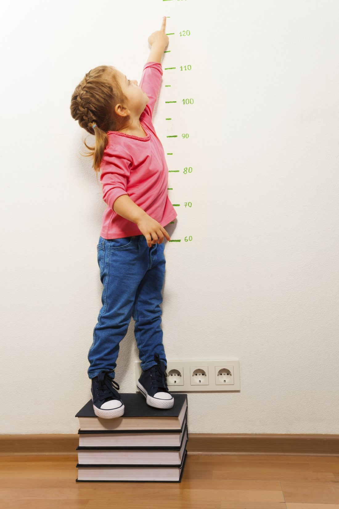 Funny girl measuring her height supporting at four big books pointing to the ruler with her finger
