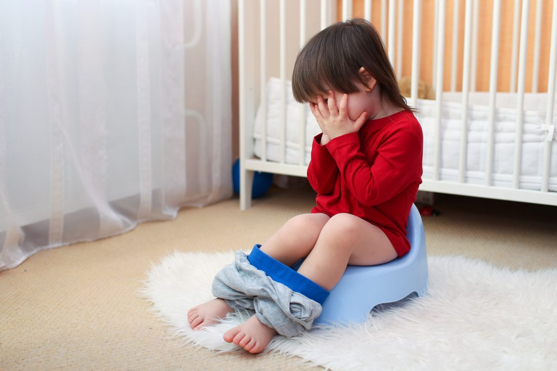 crying little child sitting on potty at home